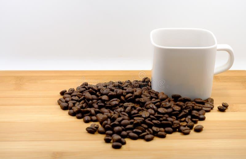 Feijões de café no copo de café imagem de stock royalty free