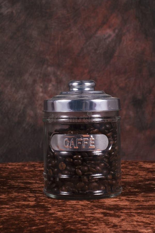 Feijões de café no frasco de vidro imagens de stock royalty free