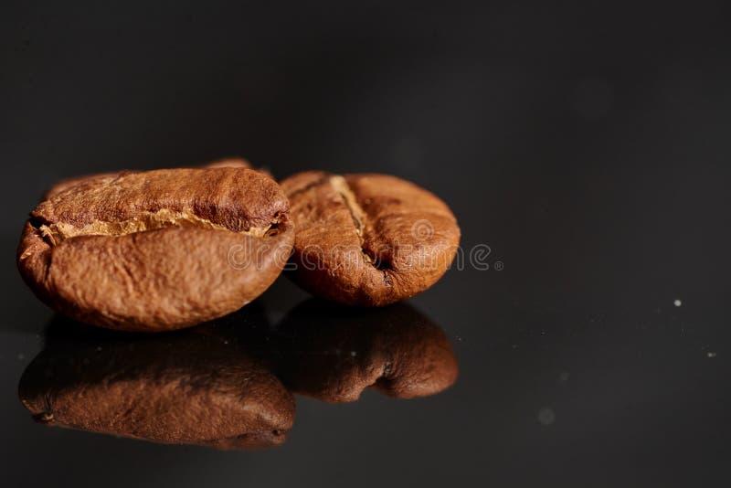 Feijões de café no fundo preto consistente com fotografia de stock