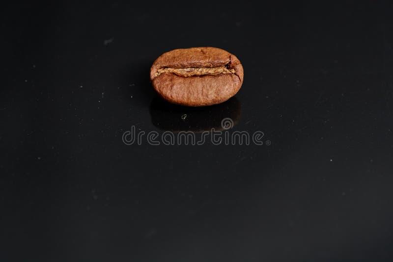 Feijões de café no fundo preto consistente com imagens de stock