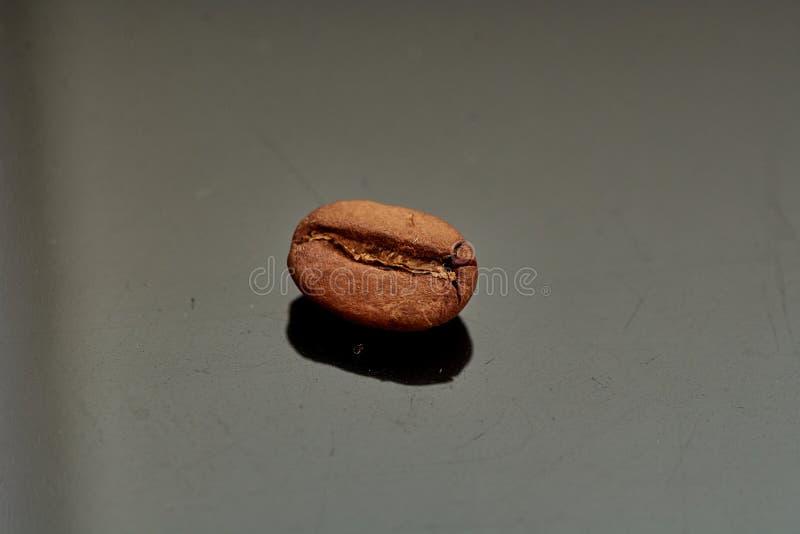 Feijões de café no fundo preto consistente com fotos de stock
