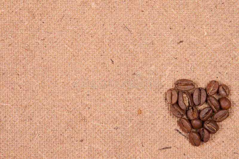Feijões de café no papel velho textured imagens de stock