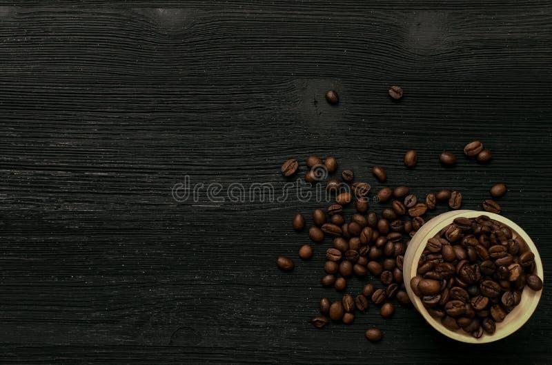 Feijões de café no potenciômetro de madeira na tabela de madeira preta imagem de stock