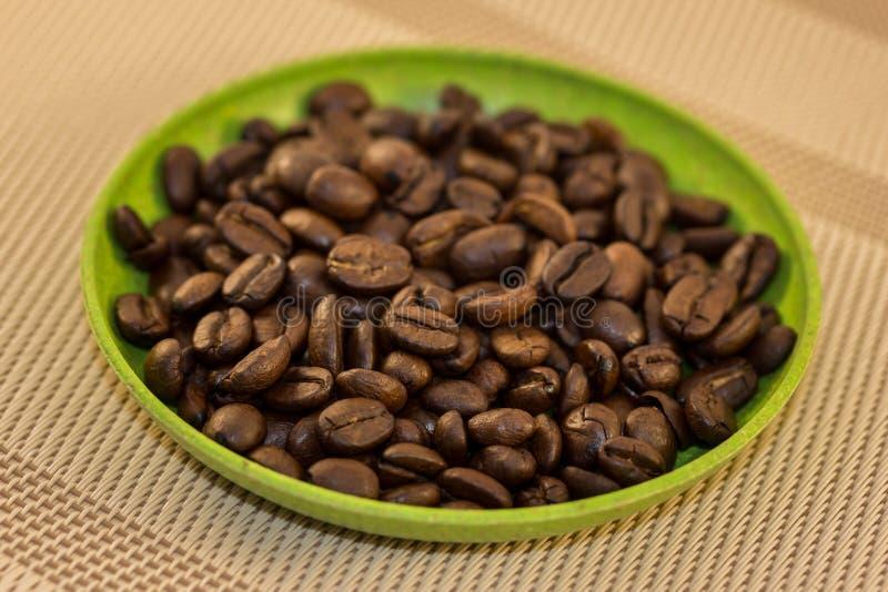 Feijões de café no prato verde fotografia de stock royalty free
