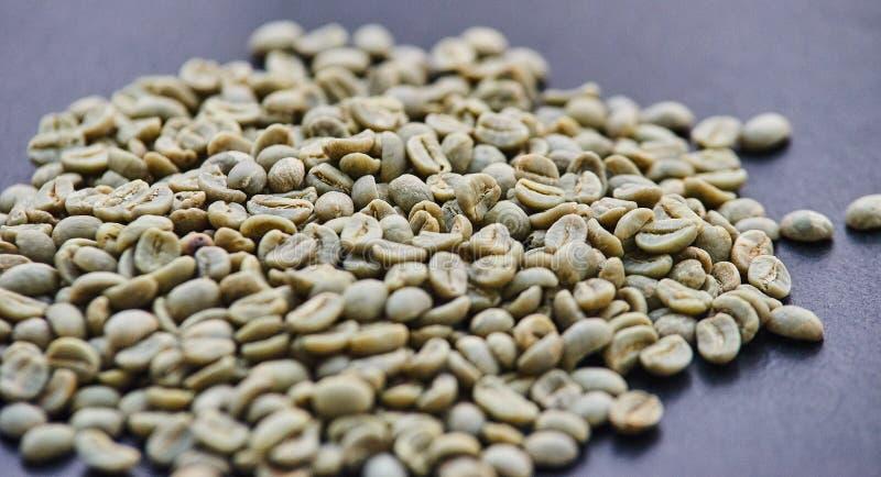 Feijões de café no volume em um fundo homogêneo imagens de stock