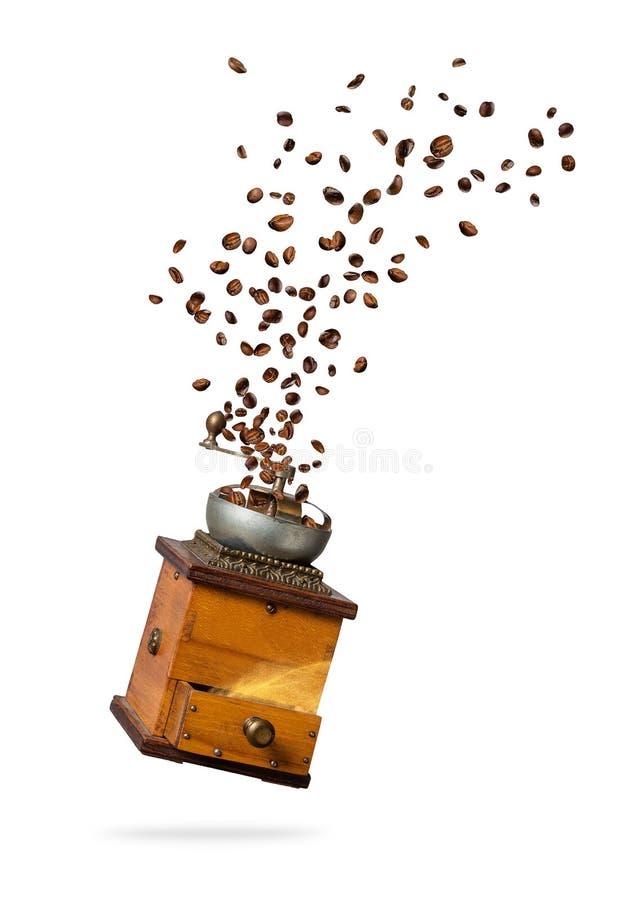 Feijões de café que voam do moedor no fundo branco imagem de stock