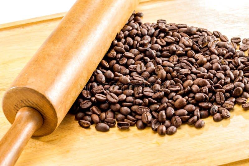 Feijões de café Roasted de Brown e pino do rolo de madeira no backgr de madeira fotos de stock royalty free