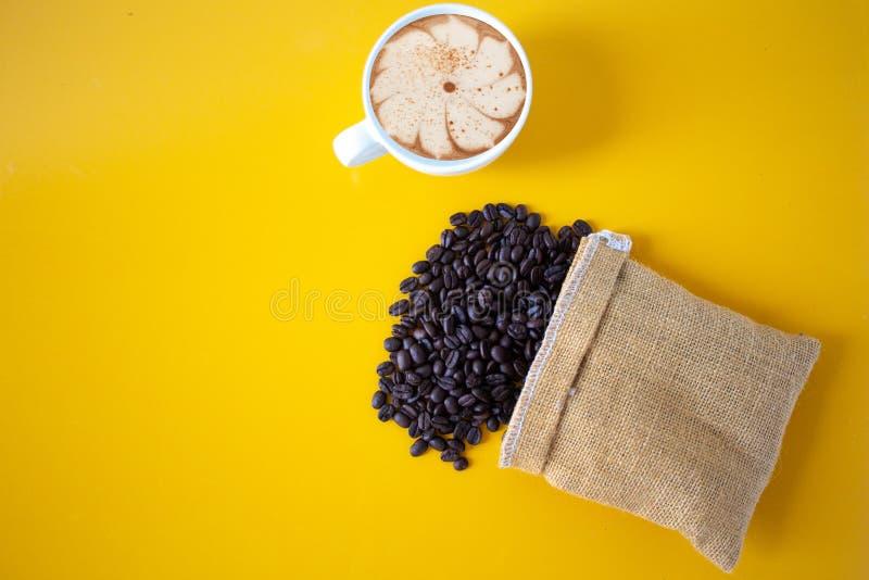 Feij?es de caf? Roasted colocados em um assoalho de madeira amarelo velho, copo de caf? da vista superior para o fundo, conceito: foto de stock
