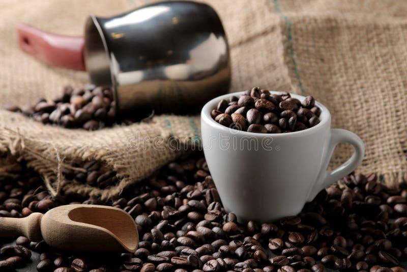 Feijões de café Roasted em um copo e em uma colher de madeira em um fundo preto Robusta, goma-arábica imagens de stock royalty free