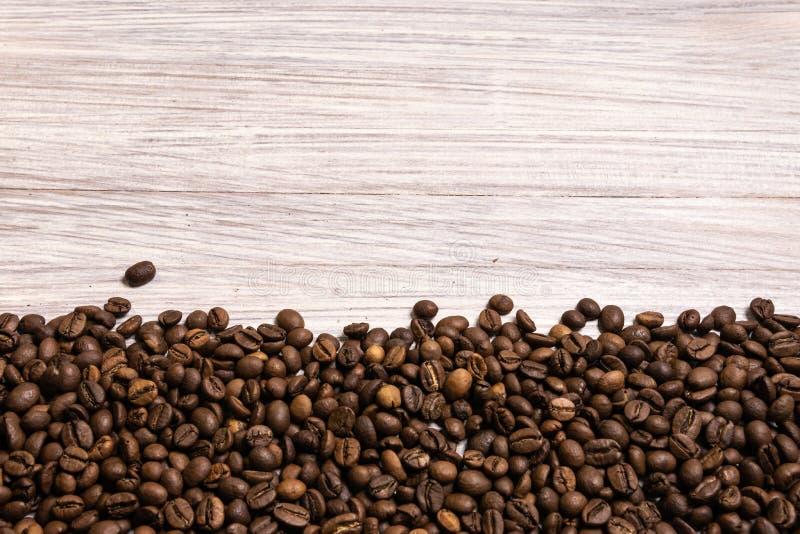 Feijões de café Roasted no volume em um fundo de madeira claro o cofee escuro roasted o café do aroma do sabor da grão, loja natu imagem de stock