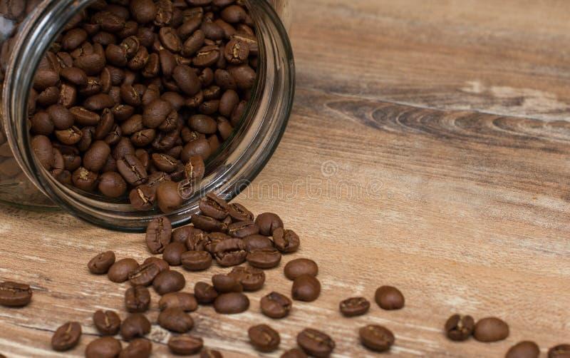 Feijões de café Roasted que caem do frasco de vidro na tabela de madeira imagens de stock