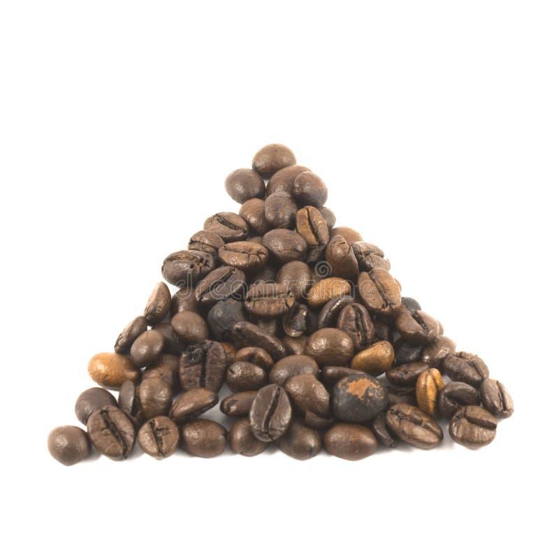Feijões de café sob a forma de um triângulo em um fundo branco fotografia de stock royalty free