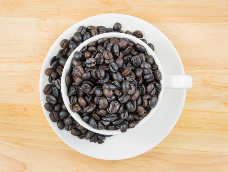 Feijões de café superiores no copo branco foto de stock