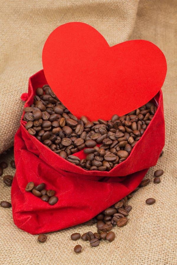 Feijões de Coffe no saco vermelho de veludo com coração vermelho fotos de stock