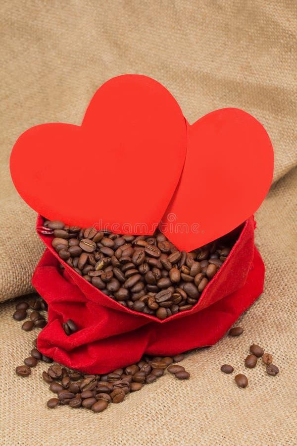 Feijões de Coffe no saco vermelho de veludo com dois corações vermelhos imagens de stock