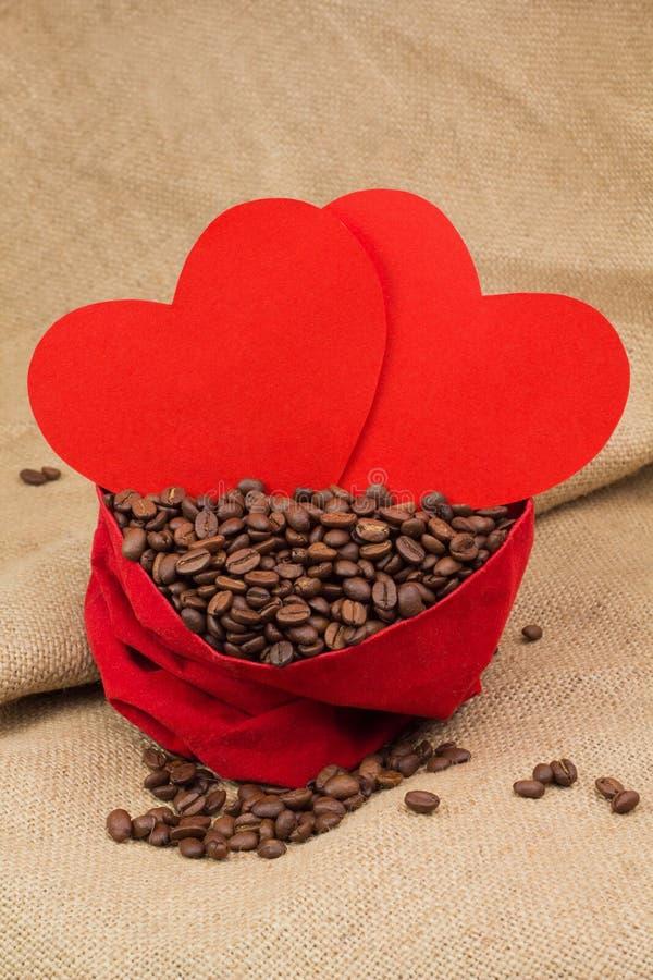 Feijões de Coffe no saco vermelho de veludo com dois corações vermelhos fotos de stock royalty free