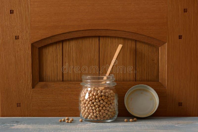 Feijões de soja no frasco de vidro imagem de stock