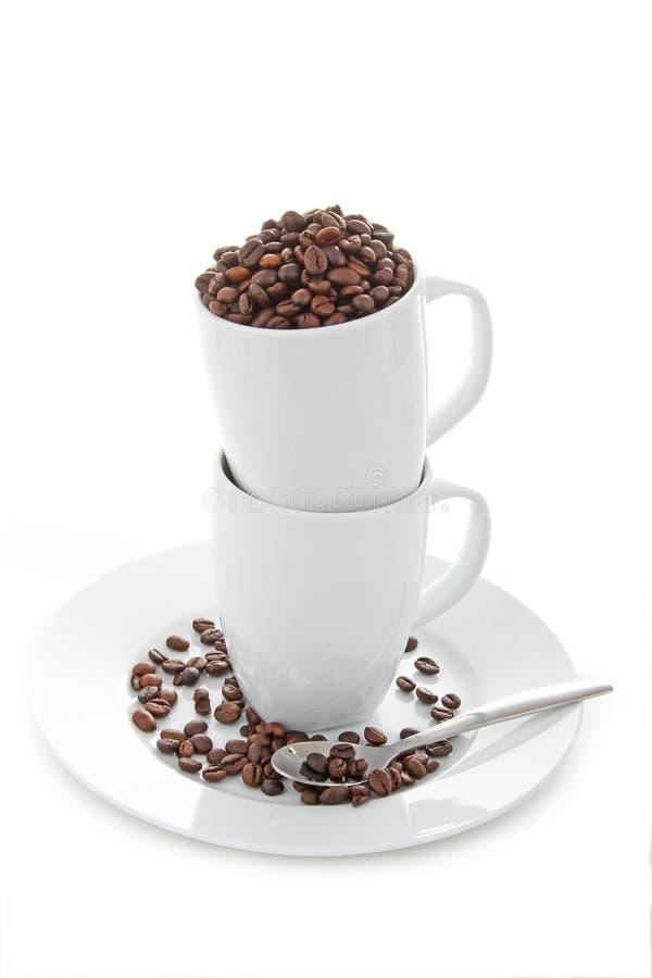 Feijões e copos de café fotografia de stock royalty free