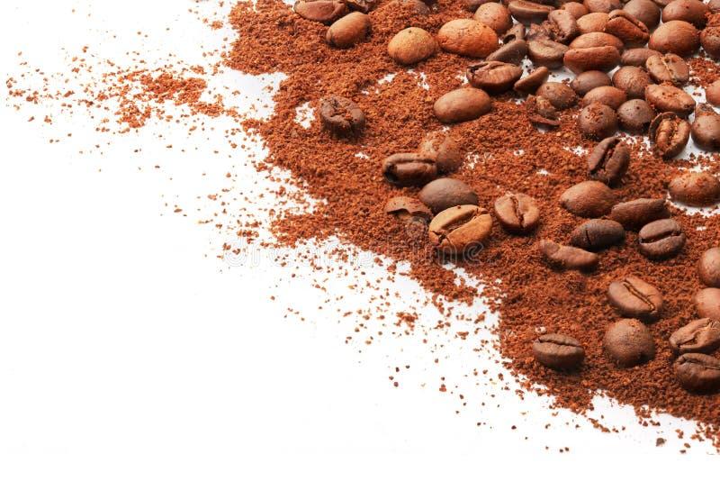 Feijões e terra inteiros de café em um fundo branco foto de stock