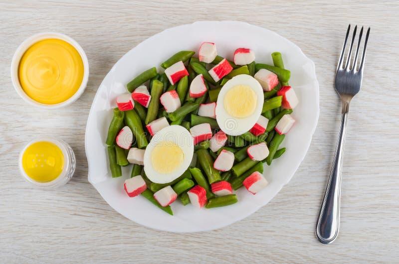 Feijões verdes com varas do caranguejo, ovos cozidos no prato, bacia com maionese, sal, forquilha na tabela Vista superior fotos de stock
