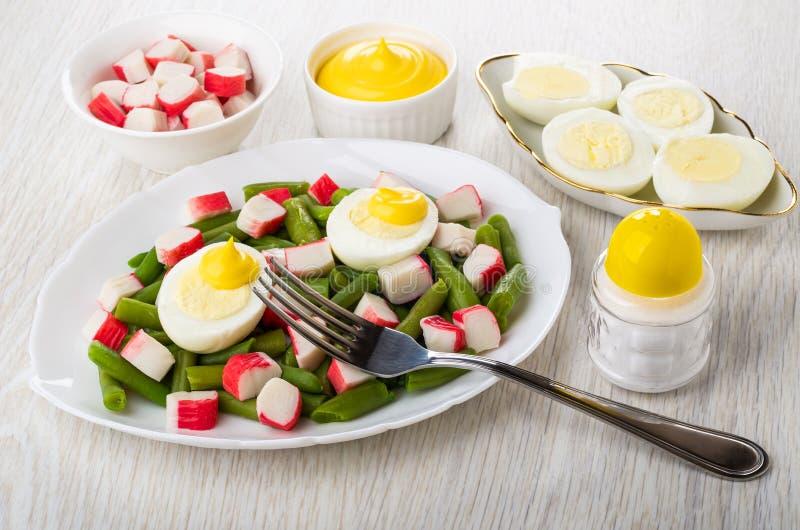 Feijões verdes com varas do caranguejo, ovos cozidos no prato, bacias com maionese, varas do caranguejo, sal, forquilha na tabela imagem de stock