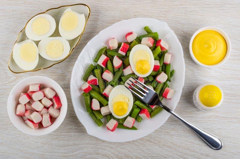 Feijões verdes com varas do caranguejo, ovos cozidos no prato, maionese, abanador de sal, forquilha na tabela Vista superior imagem de stock royalty free