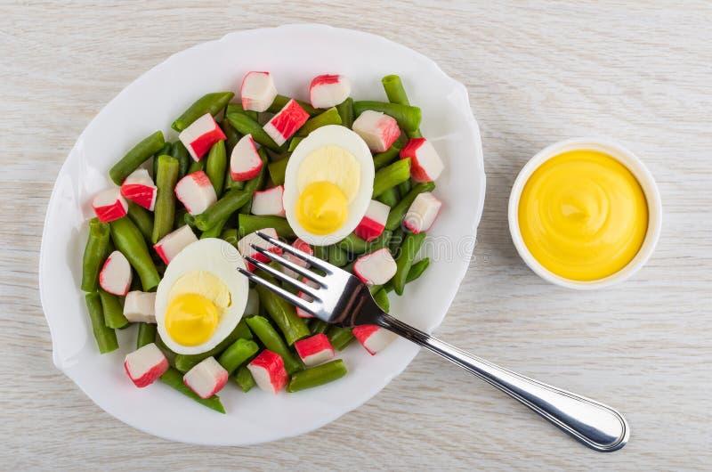 Feijões verdes com varas do caranguejo, ovos cozidos no prato, maionese, forquilha na tabela Vista superior imagem de stock royalty free