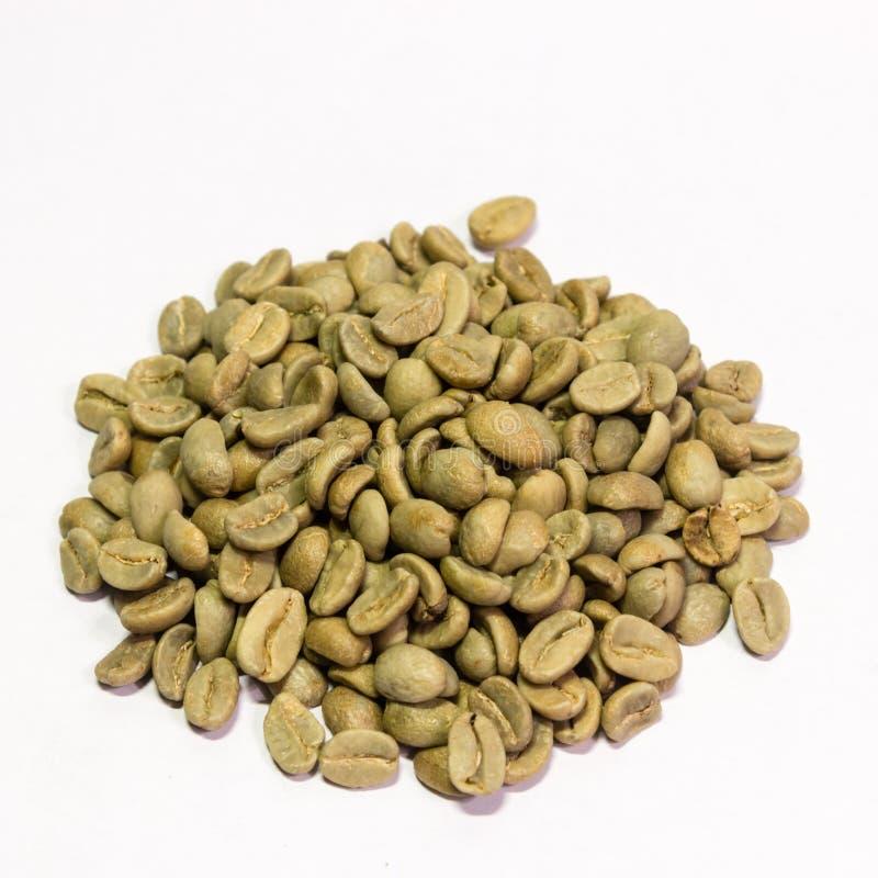 Feijões verdes do close up do café em um fundo branco fotografia de stock royalty free