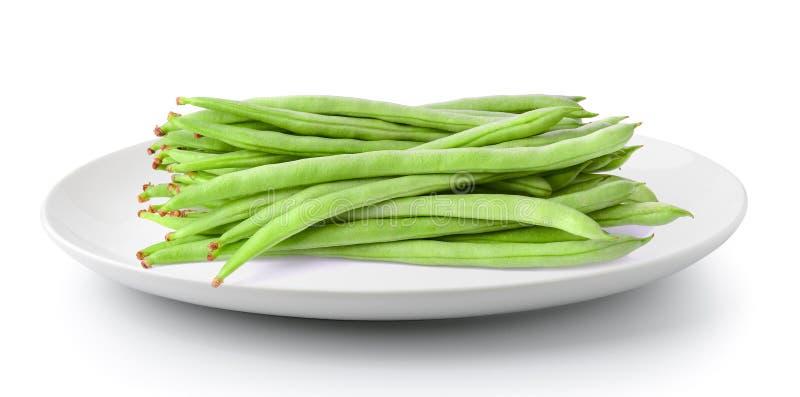 Feijões verdes em uma placa isolada em um fundo branco foto de stock