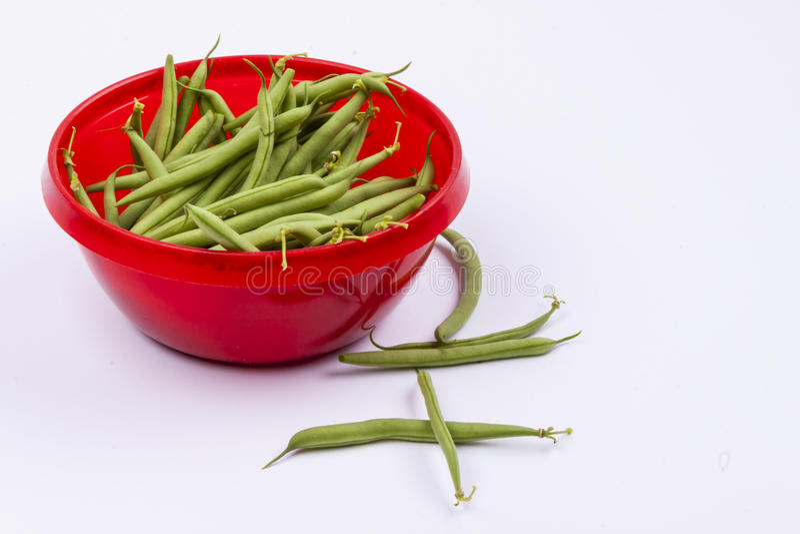 Feijões verdes na bacia vermelha - fundo branco fotos de stock