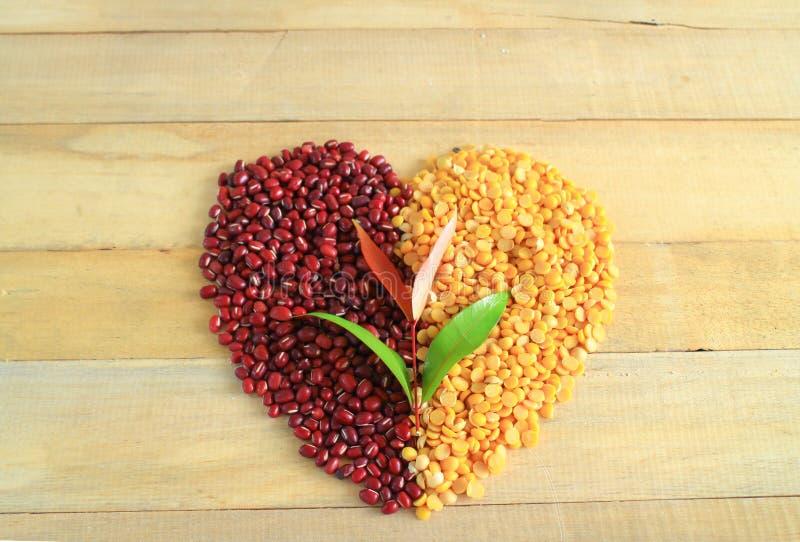 Feijões vermelhos com descascado - os feijões rachados da soja fizeram o símbolo do coração no fundo de madeira fotos de stock