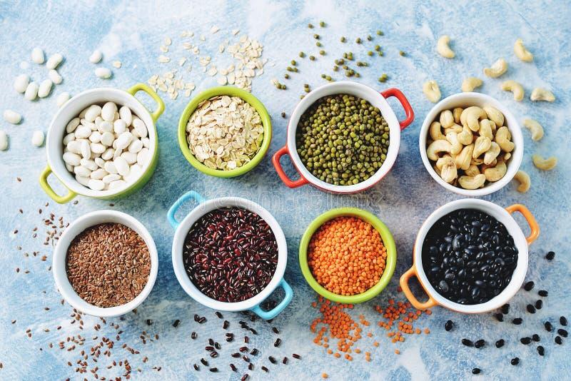 Feij?es de lentilhas vermelhas, de ervilhas, pretos, brancos e vermelhos, porcas - o conceito do alimento saud?vel do vegetariano imagem de stock