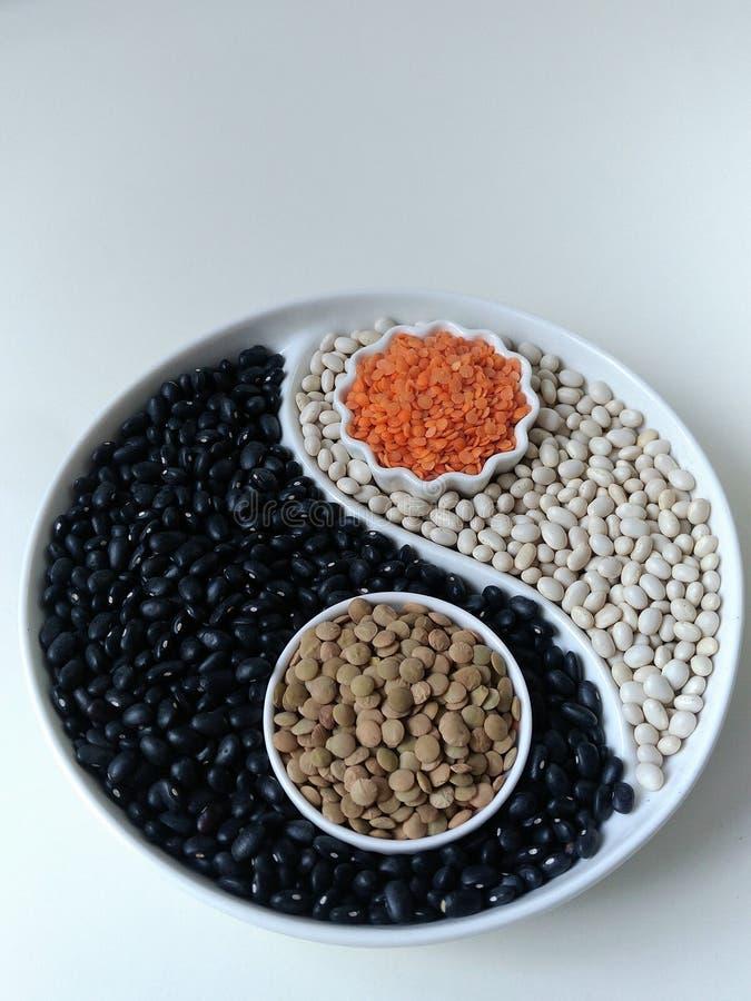 Feij?es e lentilhas na exposi??o com um separador sob a forma de Yin Yang flatley Foodfoto fotografia de stock royalty free