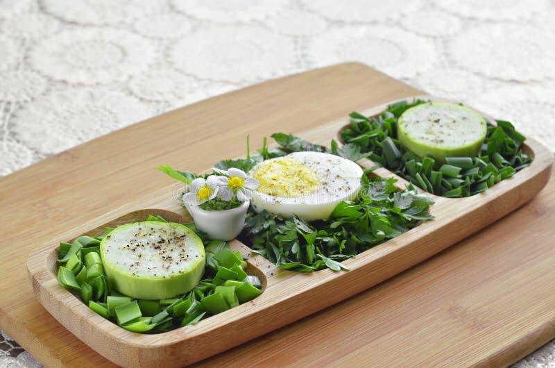 Fein gehackte verschiedene Grüns mit Ei und roher Zucchini in einer hölzernen Platte lizenzfreies stockbild