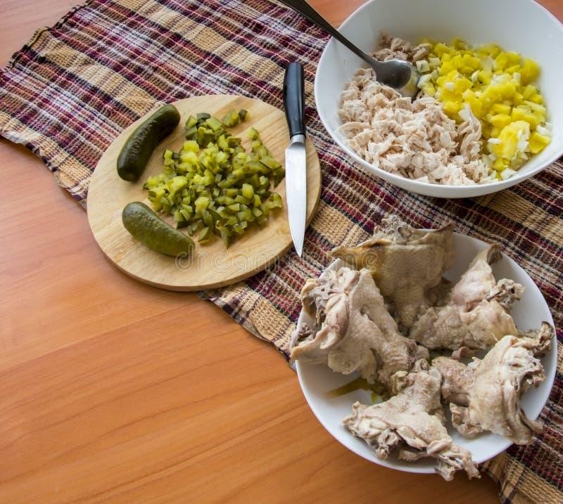 Fein gehackter Salat in einer Schüssel in Essig eingelegte Gurke auf dem Brett stockbilder