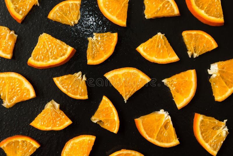 Fein geschnittene Tangerinen auf einem nass schwarzen Hintergrund stockfotografie