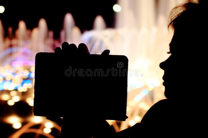 Feines Mädchen auf der Straße mit Tablette, Hinweisschild in den Händen stockfoto