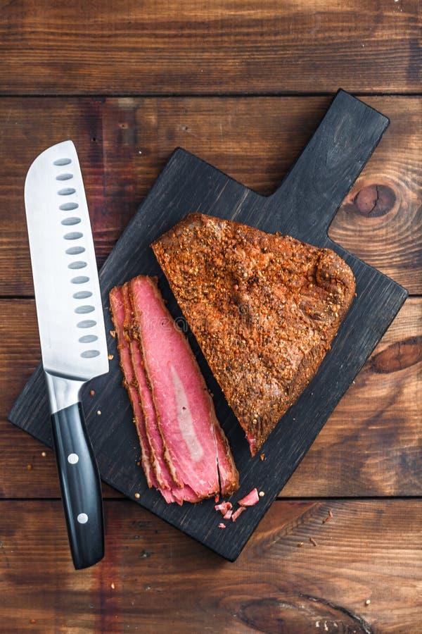 Feinkostgeschäft-Rindfleischpastrami geschnitten auf hölzernem Brett lizenzfreies stockbild