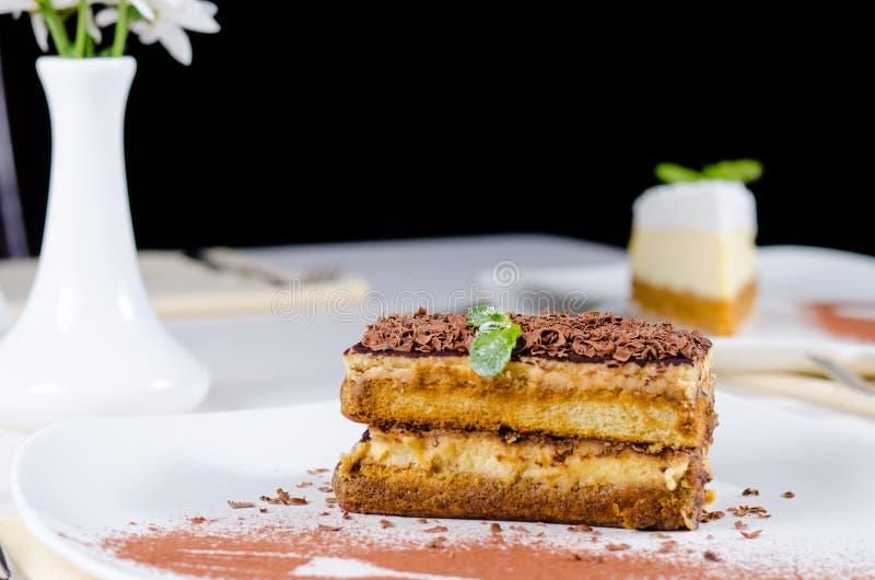 Feinschmecker-überlagerter Kuchen auf Platte mit Kakaopulver lizenzfreies stockfoto