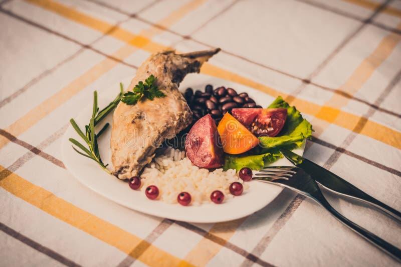Feinschmecker briet Kaninchenbein mit Reis und Bohnen, weiße Soße Mahlzeit wird auf Platte des Weiß einfach und überprüfter Tisch stockfotografie