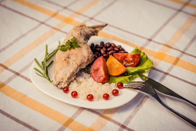 Feinschmecker briet Kaninchenbein mit Reis und Bohnen, weiße Soße Mahlzeit wird auf Platte des Weiß einfach und überprüfter Tisch lizenzfreies stockbild