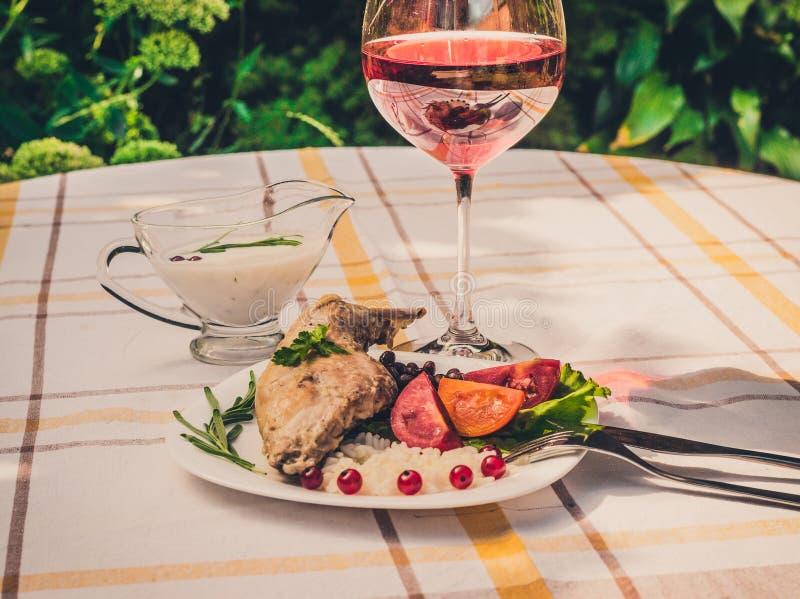 Feinschmecker briet Kaninchenbein mit Reis und Bohnen Weiße Soße und Glas Rotwein Mahlzeit wird auf Weiß einfach Platte und check lizenzfreie stockbilder