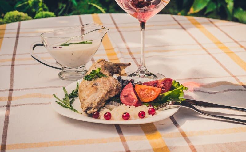 Feinschmecker briet Kaninchenbein mit Reis und Bohnen Weiße Soße und Glas Rotwein Mahlzeit wird auf Weiß einfach Platte und check lizenzfreies stockbild