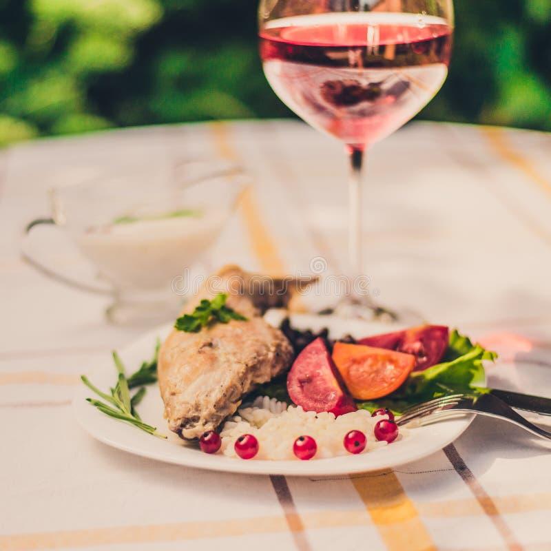 Feinschmecker briet Kaninchenbein mit Reis und Bohnen Weiße Soße und Glas Rotwein Mahlzeit wird auf Weiß einfach Platte und check stockfotos