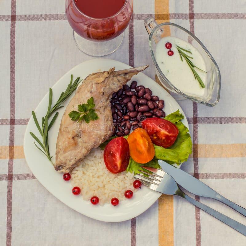 Feinschmecker briet Kaninchenbein mit Reis und Bohnen Weiße Soße und Glas Tomatensaft Mahlzeit wird auf Platte des Weiß einfach u stockfoto