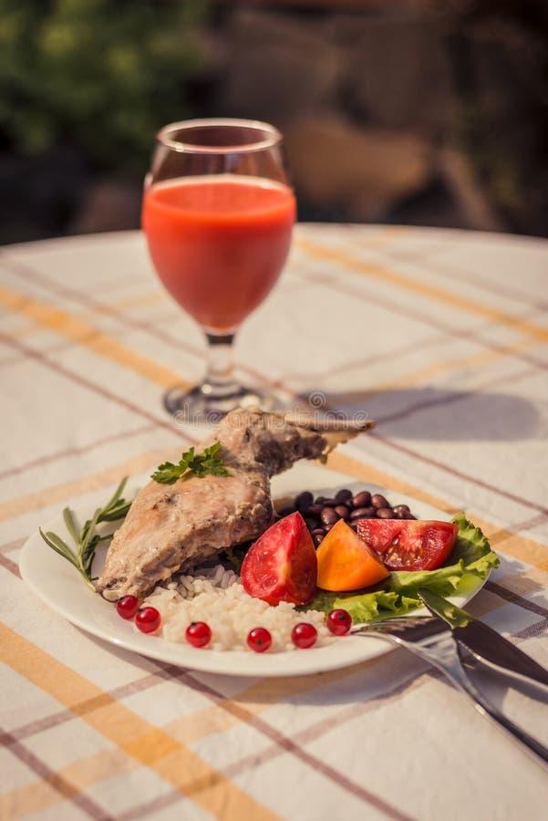 Feinschmecker briet Kaninchenbein mit Reis und Bohnen Weiße Soße und Glas Tomatensaft Mahlzeit wird auf Platte des Weiß einfach u stockbild