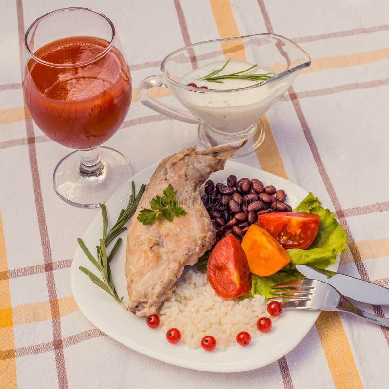 Feinschmecker briet Kaninchenbein mit Reis und Bohnen Weiße Soße und Glas Tomatensaft Mahlzeit wird auf Platte des Weiß einfach u lizenzfreies stockfoto