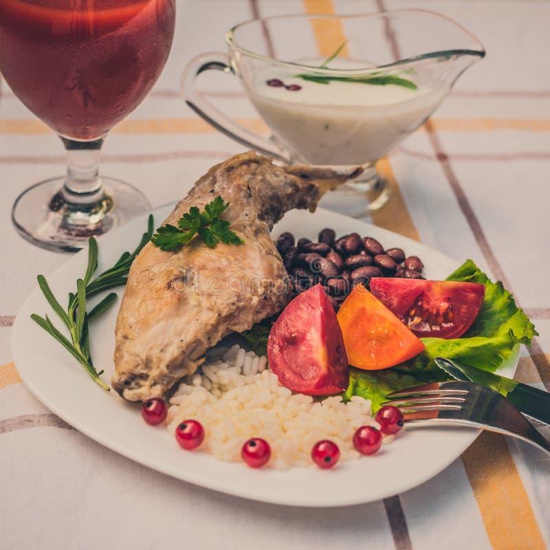 Feinschmecker briet Kaninchenbein mit Reis und Bohnen Weiße Soße und Glas Tomatensaft Mahlzeit wird auf Platte des Weiß einfach u lizenzfreie stockfotos