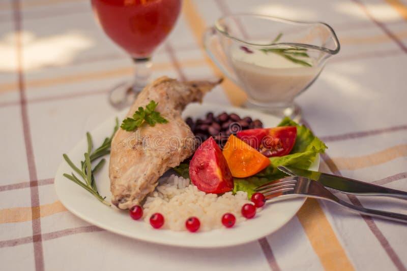 Feinschmecker briet Kaninchenbein mit Reis und Bohnen Weiße Soße und Glas Tomatensaft Mahlzeit wird auf Platte des Weiß einfach u stockfotos