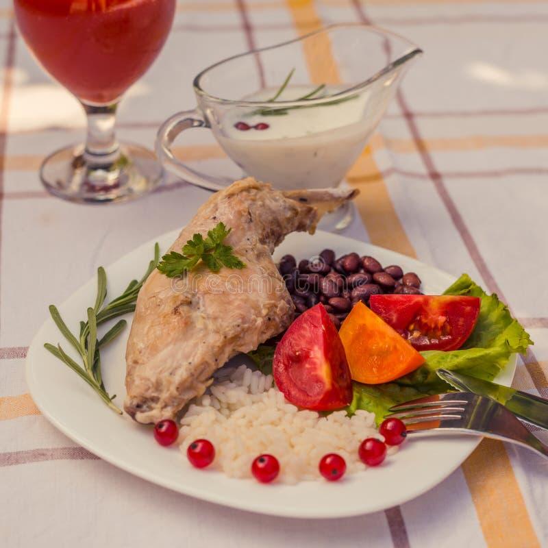 Feinschmecker briet Kaninchenbein mit Reis und Bohnen Weiße Soße und Glas Tomatensaft Mahlzeit wird auf Platte des Weiß einfach u lizenzfreie stockfotografie